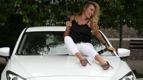 Härlig ung kvinna med långt sammanträde för blont hår på huven av den vita bilen med paraplyet i regnig sommardag långsamt arkivfilmer