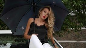 Härlig ung kvinna med långt sammanträde för blont hår på huven av den vita bilen med paraplyet i regnig sommardag långsamt stock video