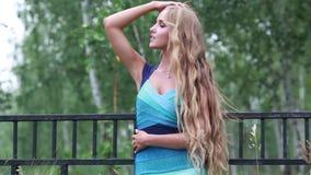 Härlig ung kvinna med långt vitt hår i en parkera stock video