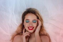 Härlig ung kvinna med ljus makeup med stängda ögondrömmar av något som är angenäm royaltyfri bild