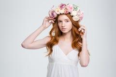 Härlig ung kvinna med lockigt rött hår i blommakrans royaltyfria foton