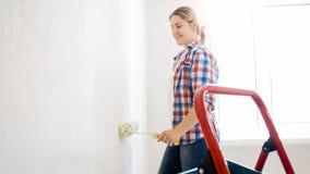 Härlig ung kvinna med målarfärgrullen som gör renovering på det nya huset arkivbild