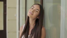 Härlig ung kvinna med mörkt hår som ler på kamera stock video