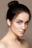 Härlig ung kvinna med perfekt ren skinande hud, naturlig modemakeup Glamourstående av modellen med den gulliga bullefrisyren royaltyfri bild