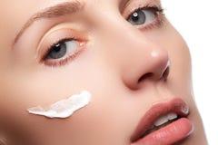 Härlig ung kvinna med ren ny hudnärbild Härligt kvinnaframsidaslut upp studio på vit Ung kvinna med kosmetisk cre Fotografering för Bildbyråer