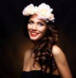 Härlig ung kvinna med rosa blommor för sommar Långt Permed lockigt hår och modemakeup skönhet blommar flickan Arkivfoton