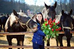 Härlig ung kvinna med rosor och svarthästar Arkivfoton