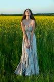 Härlig ung kvinna med solrosen som poserar i solrosorna fi arkivbilder