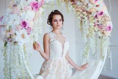 Härlig ung kvinna med stilfullt brunetthår och eleganta klänningen som poserar i lyxig vit klassisk ruminre med Royaltyfri Bild