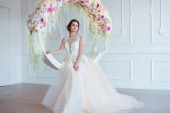 Härlig ung kvinna med stilfullt brunetthår och eleganta klänningen som poserar i lyxig vit klassisk ruminre med Royaltyfria Bilder