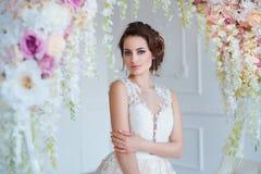 Härlig ung kvinna med stilfullt brunetthår och eleganta klänningen som poserar i lyxig vit klassisk ruminre med Arkivbilder