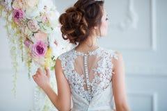 Härlig ung kvinna med stilfullt brunetthår och eleganta klänningen som poserar i lyxig vit klassisk ruminre med Royaltyfria Foton