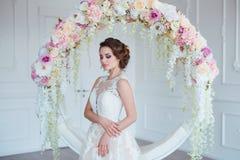 Härlig ung kvinna med stilfullt brunetthår och eleganta klänningen som poserar i lyxig vit klassisk ruminre med Royaltyfri Foto