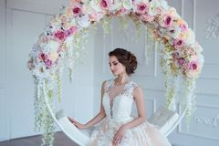 Härlig ung kvinna med stilfullt brunetthår och eleganta klänningen som poserar i lyxig vit klassisk ruminre med Arkivfoton