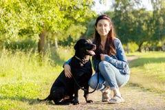 Härlig ung kvinna med svarta labrador retriever Arkivbilder