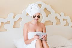 Härlig ung kvinna med under-lappar och att använda mobiltelefonen eller att skriva för öga smsmassage i badrocken som ligger i sä royaltyfri foto