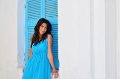 Härlig ung kvinna mot det vita Grekland huset med det blåa fönstret Arkivfoto