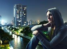 Härlig ung kvinna mot en stad vid natt Arkivfoto