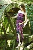 Härlig ung kvinna och gammal watermill royaltyfria foton