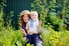 Härlig ung kvinna och hennes förtjusande liten son som tycker om skörden Arkivbild