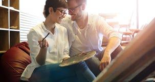 Härlig ung kvinna och stilig en man som tillsammans deltar i ett målningseminarium arkivbild