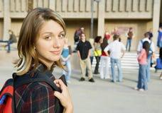 Härlig ung kvinna på högskolauniversitetsområde arkivfoton