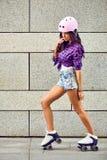 Härlig ung kvinna på rullskridskor och en rosa hjälm fotografering för bildbyråer