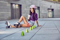 Härlig ung kvinna på rullskridskor och kaffekoppen Arkivfoton