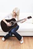 Härlig ung kvinna på soffan med en gitarr fotografering för bildbyråer