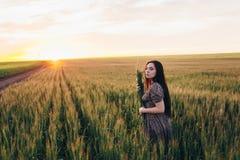 Härlig ung kvinna på solnedgången i fältet Royaltyfri Bild
