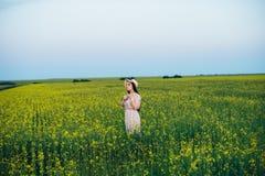 Härlig ung kvinna på solnedgången i fältet Royaltyfria Bilder