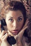 Härlig ung kvinna på telefonen i vardagsrum royaltyfri bild