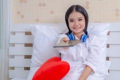 Härlig ung kvinna som är lycklig med hörlurar och minnestavlor som håller ögonen på filmer på minnestavlan i säng royaltyfri bild