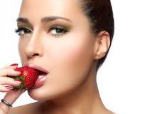 Härlig ung kvinna som äter jordgubben arkivbild