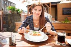 Härlig ung kvinna som äter lasagne i restaurang Arkivfoto