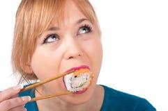 Härlig ung kvinna som äter sushi med pinnar Fotografering för Bildbyråer