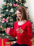 Härlig ung kvinna som öppnar en julklapp Arkivbilder