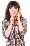 Härlig ung kvinna som använder den retro orange telefonen royaltyfri foto