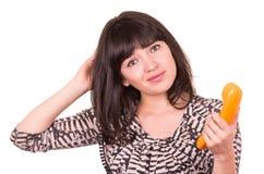 Härlig ung kvinna som använder den retro orange telefonen royaltyfri bild