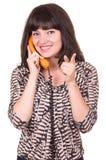 Härlig ung kvinna som använder den retro orange telefonen fotografering för bildbyråer