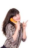 Härlig ung kvinna som använder den retro orange telefonen arkivfoto
