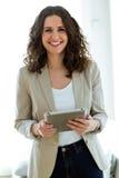 Härlig ung kvinna som använder hennes digitala minnestavla i kontoret Royaltyfri Fotografi