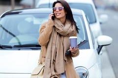 Härlig ung kvinna som använder hennes mobiltelefon i gatan Arkivfoton