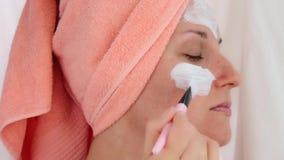 Härlig ung kvinna som applicerar en kosmetisk maskering med en borste stock video