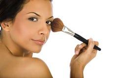 Härlig ung kvinna som applicerar fundamentpulver eller rodnad med makeupborsten som isoleras på vit bakgrund Royaltyfri Foto