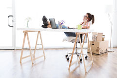 Härlig ung kvinna som arbetar i hennes nya kontor Arkivfoto