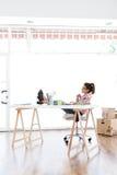 Härlig ung kvinna som arbetar i hennes nya kontor Royaltyfri Foto