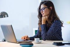 Härlig ung kvinna som arbetar med bärbara datorn i hennes kontor Royaltyfri Fotografi