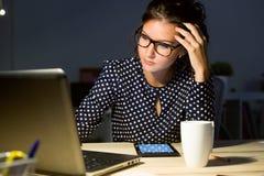 Härlig ung kvinna som arbetar med bärbara datorn i hennes kontor på natten Royaltyfri Foto