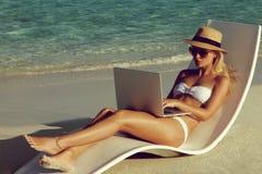 Härlig ung kvinna som arbetar med bärbara datorn på den tropiska stranden fotografering för bildbyråer